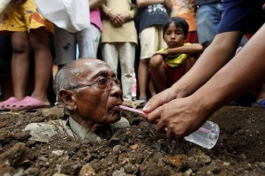 Dadang, a resident of Cempaka Putih district, drinks water after being buried in the ground in Jakarta