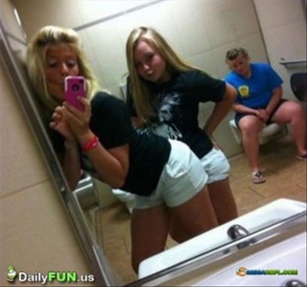 1 two women taking picture in bathroom mirror, someone is going to the bathroom