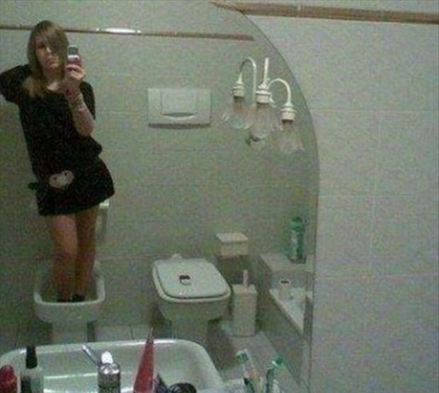 2 woman standing in a toilet, taking a picture of herself in the mirror