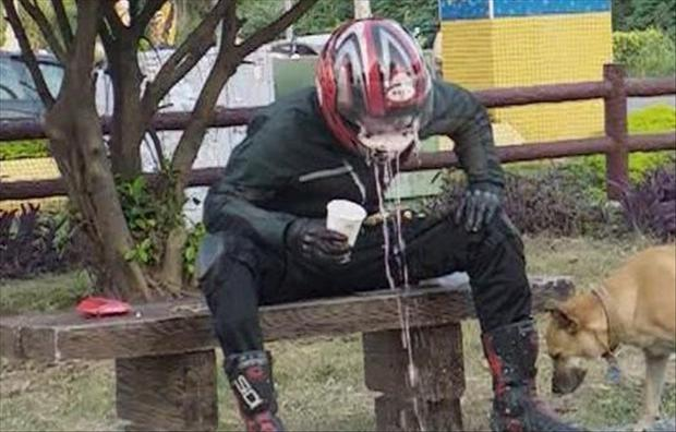 man throwing up in his helmet, having a bad day
