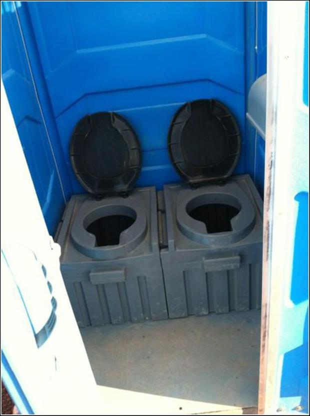 two toilets, in a porta potty outhouse
