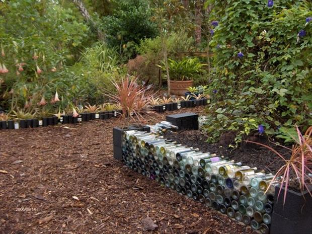 a raised garden made from wine bottles