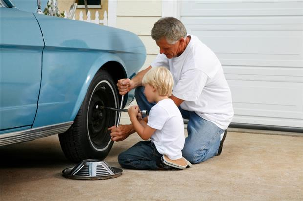 dad showing his son how to change a tire