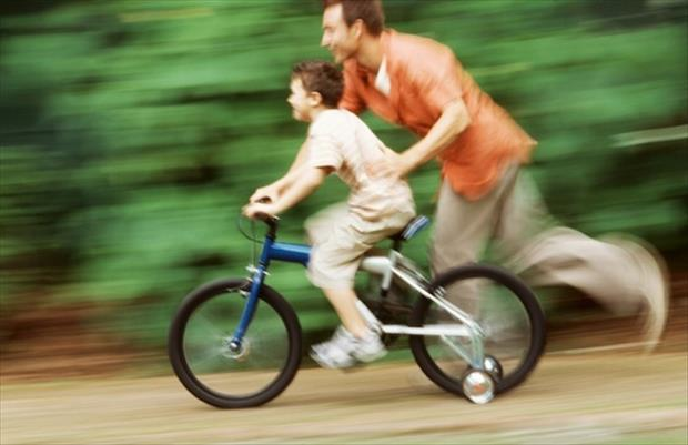 good dad teaches son to ride a bike