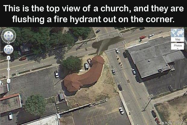 This is the top view of a church and they are flushing a fire hydrant on the corner